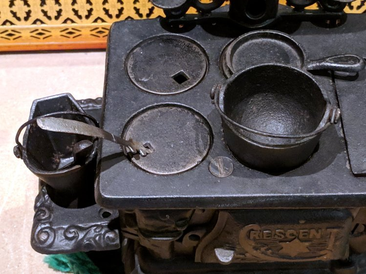 Toy stove with repaired lid lifter